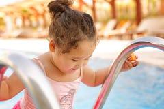 Kazakh little girl playing near swimming pool. Pretty little kazakh curly girl playing by the swimming pool Stock Photos