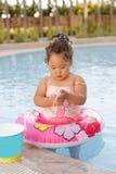 Kazakh little girl playing near swimming pool. Pretty little kazakh curly girl playing by the swimming pool Royalty Free Stock Images