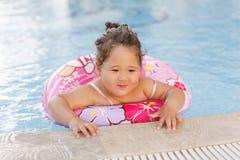 Kazakh little girl playing near swimming pool. Pretty little kazakh curly girl playing by the swimming pool Royalty Free Stock Photos