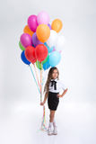 Pretty little school girl standing with balloons Royalty Free Stock Image
