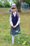 Pretty little school girl in uniform poses in school park Royalty Free Stock Images