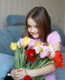Pretty little shy girl holding big bouquet of tulips royalty free stock images