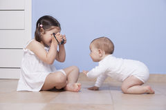 Pretty little sister taking pictures to her baby brother stock photography