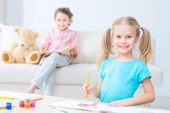 Pretty little sisters painting stock image