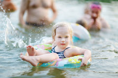 Pretty little toddler girl swimming Stock Images