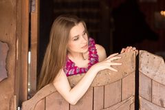 Pretty long hair Cowgirl standing in saloon entrance Royalty Free Stock Photos
