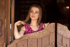 Pretty long hair Cowgirl standing in saloon entrance Royalty Free Stock Image