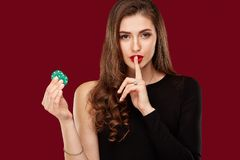 Pretty long hair woman in black dress holding chips for gambling Stock Images