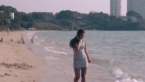 Pretty long haired brunette in gray dress walks barefoot. On ocean sandy beach on sunny tropical day stock video