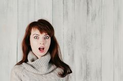 A pretty long haired girl in a gray pullover, surprised big eyes. A beautiful young brunette woman in a gray pullover, surprised big eyes, open mouth, with light Stock Photos