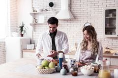 Pretty long-haired young woman and her dark-haired husband preparing salad together royalty free stock photos