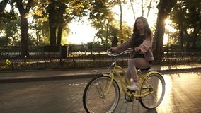 Pretty longhaired girl riding a bike on the street or boulevard in summer city park. Wearing pink coloured casual stock video