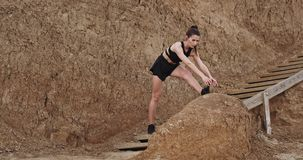 Pretty looking young woman exercises stretching poses on wooden steps with amazing rocks on the background.  stock footage