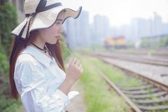 Pure and lovely Asian girl. Pretty lovely girl and rail background. She looked at the rails and her face was full of thoughts royalty free stock photography
