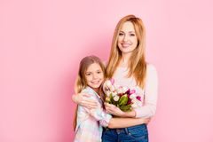 Pretty, lovely mom and daughter celebrating women`s day, embraci. Ng over oink background, holding colorful tulips, looking at camera, leisure, happiness, fun Royalty Free Stock Photography