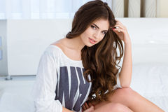 Pretty lovely woman sitting and posing on bed in hotel Royalty Free Stock Image
