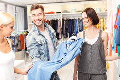 Pretty loving couple choosing clothes in shop. Young men is offering his girlfriend to buy blue dress. He is standing and holding clothing with confidence. Woman Stock Image