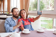 Pretty loving couple is making fun in cafe Stock Photos