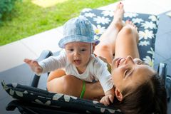 Pretty loving mom trying to soothe scarred crying baby in mother`s arms outdoor at sun deck chair stock photos