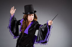 Pretty magician girl holding stick against gray Royalty Free Stock Photography