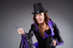 Pretty magician girl holding stick against gray Royalty Free Stock Photo
