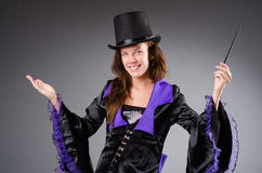 Pretty magician girl holding stick against gray Royalty Free Stock Photos
