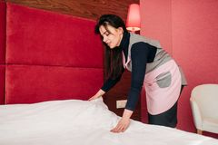 Pretty maid makes the bed in the hotel room. Pretty maid in uniform makes the bed in the hotel room. Cleaning service, professional housekeeping, charwoman works stock image