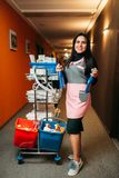 Pretty maid rolls the cart with detergents. Pretty maid in uniform rolls the cart with detergents along the corridor of hotel. Cleaning service, professional royalty free stock photos