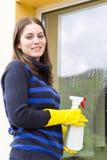 Pretty maid washing house windows Stock Photo