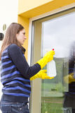 Pretty maid washing house windows. Young female maid in yellow gloves washing facade windows with spray cleaner stock photo