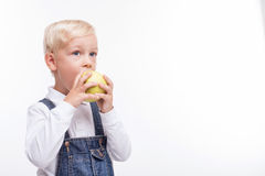 Pretty male child is eating green fruit stock photo