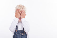 Pretty male child is trying not to see something. Cheerful boy is standing and covering his eyes with his arms. He is smiling shyly. The boy is expecting a big royalty free stock images