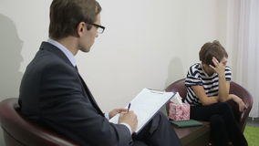 Pretty male psychiatrist looking at patient during her visit stock video footage