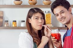 Pretty man feeding strawberry smoothie to his girlfriend royalty free stock photography