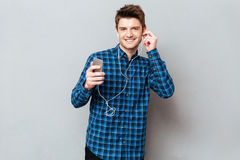 Pretty man looking camera while listening music. Young pretty student looking camera while listening music on smartphone with headphones royalty free stock photo
