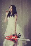 Pretty maniac. Bloody beautiful girl posing with chainsaw and chamomile royalty free stock photography