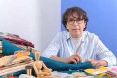 Mature brunette woman sewing patchwork. A pretty mature brunette woman sewing patchwork Stock Photos
