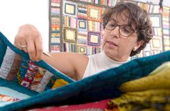 Mature brunette woman sewing patchwork. A pretty mature brunette woman sewing patchwork Royalty Free Stock Photo