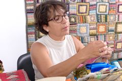 Mature brunette woman sewing patchwork. A pretty mature brunette woman sewing patchwork Royalty Free Stock Photos