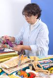 Mature brunette woman sewing patchwork. A pretty mature brunette woman sewing patchwork Stock Image