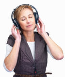 Pretty mature lady enjoying music on headphones Stock Photos