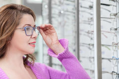 Pretty mature lady is trying on spectacles stock image