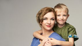Pretty mature mom with cute baby boy. Piggyback portrait together. Mother parent hugging.  royalty free stock image