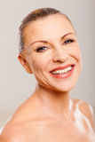 Mature woman beauty. Pretty mature woman beauty smiling against plain background Royalty Free Stock Photography