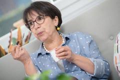 Pretty mature woman eating a yogurt at home. A pretty mature woman eating a yogurt at home Stock Image