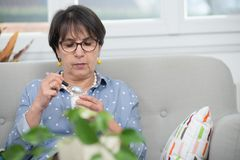 Pretty mature woman eating yogurt at home. Pretty mature woman eating a yogurt at home Royalty Free Stock Image
