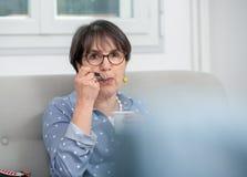 Pretty mature woman eating  yogurt at home. Pretty mature woman eating a yogurt at home Stock Image