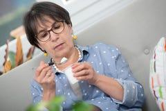 Pretty mature woman eating  yogurt at home. Pretty mature woman eating a yogurt at home Stock Photo