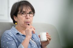 Pretty mature woman eating yogurt at home. Pretty mature woman eating a yogurt at home Royalty Free Stock Photos