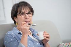 Pretty mature woman eating a yogurt at home. A pretty mature woman eating a yogurt at home Stock Photos